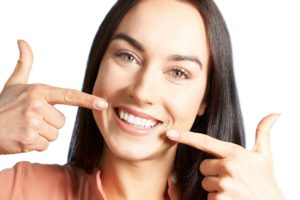 Woman at cosmetic dentist in Louisville pointing to beautiful teeth.