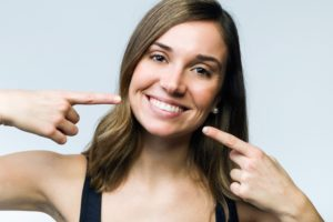 Woman pointing to her smile after cosmetic dental treatments.