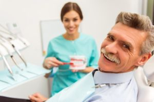 older man smiling in dental chair with dental implants