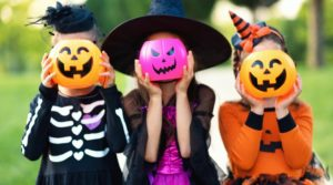 three little kids holding plastic jack-o-lanterns in front of their faces